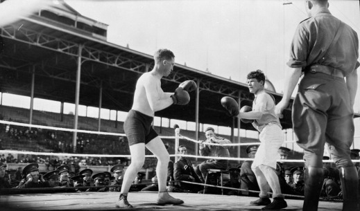 A black-and-white photograph of two soldiers boxing. One wears black trunks and the other wears white trunks. Soldiers outside the ring watch the match.