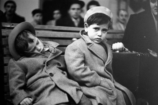 A black-and-white photograph of two small boys wearing wool coats and hats sitting on a wooden bench. One is slumped over sleeping; the other is staring the camera and holding a suitcase. A blurred crowd of people can be seen in the background.