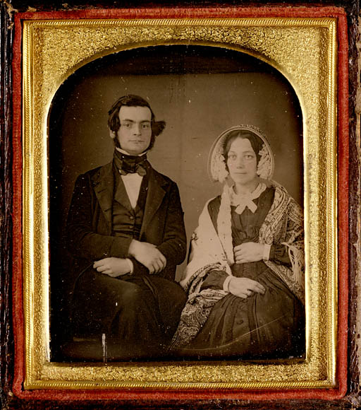 A colour photograph of a sepia-tone image in a wood and gold frame showing a seated man and woman. The man is wearing a suit, waistcoat and cravat. The woman is wearing a bonnet, dress and patterned shawl.