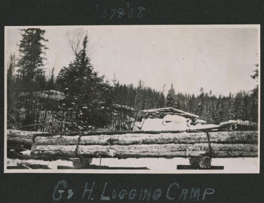 A black-and-white photograph of a Gilmour and Hughson logging camp during the winter. Log shelters are in the background along a line of trees. Fresh cut timber is stacked and chained in the foreground.