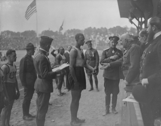 A black-and-white photograph of a man dressed in athletic wear, surrounded by other men in similar attire or in uniforms, receiving a medal from an older man in military dress.