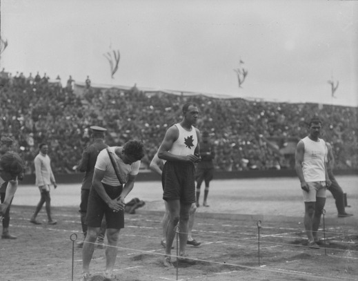 A black-and-white photograph of a group of runners at the starting line. One is wearing a white shirt with a maple leaf on the front.