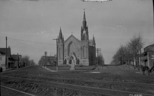 Black-and-white photo of a large church in a small village. Railway tracks can be seen in the foreground.