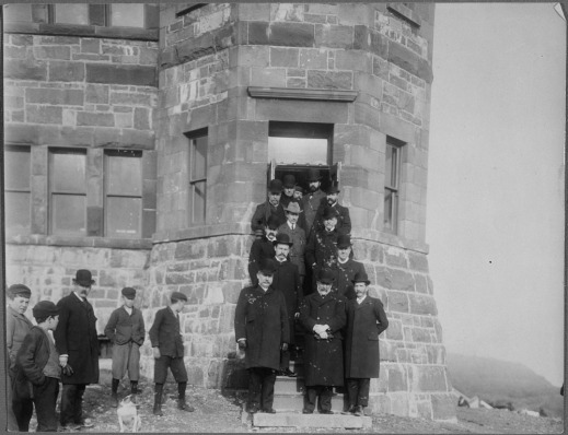 A black-and-white photograph of Guglielmo Marconi posing on the steps of a building with 12 members of the administration of Newfoundland, Signal Hill, St. John's.