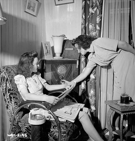 A black-and-white photograph of a two women listening to a radio. One woman sits in a chair, the second women stands and adjusts the station settings.