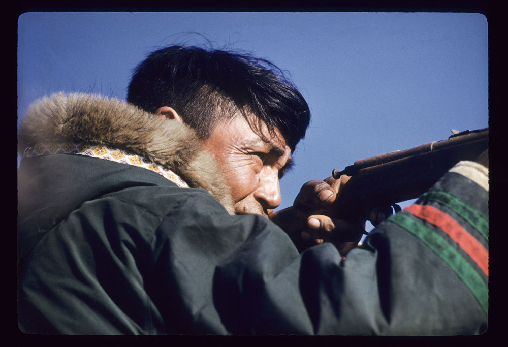 A colour photograph of a man seen in profile aiming a gun. He's wearing a traditional fur-trimmed parka with alternating green and red stripes on the sleeves.
