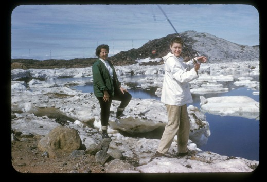 A colour photograph of two women fishing on the banks of a water body. They are standing on rocks and there are ice floes in the water.