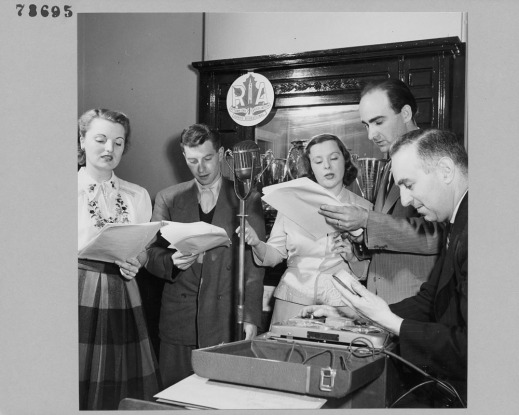 A black-and-white photograph of two women and three men, members of the R. A. Radio Acting Group, reading from a script into a microphone.