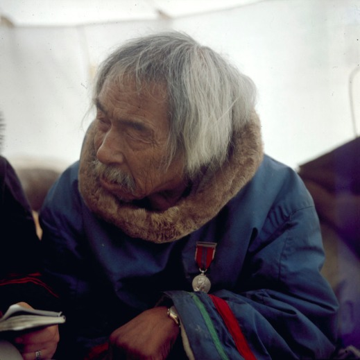 A colour photograph of an elder wearing a traditional coat with green and red stripes on the sleeves. He is also wearing a medal with an image of Queen Victoria engraved on it.