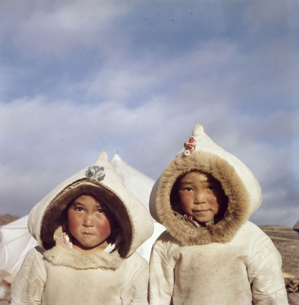 A colour photograph of two Inuit children wearing traditional coats in front of a white tent in a rocky landscape.