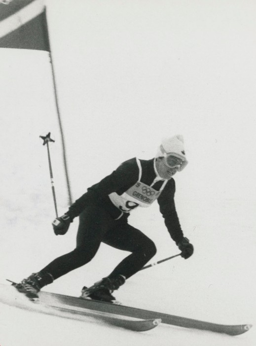 A black-and-white photograph of Nancy Greene during her gold medal run in giant slalom.