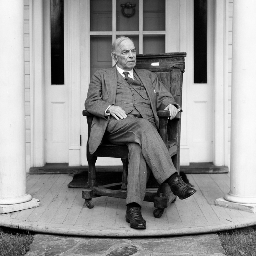 Black-and-white image of William Lyon Mackenzie King sitting on his front porch.