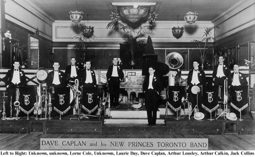 A black-and-white photograph of men dressed in formal wear standing with their musical instruments.