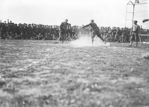 A black-and-white photograph of a player sliding into home plate. The catcher is standing over the base while the umpire makes the call. A crowd of soldiers cheers them on.