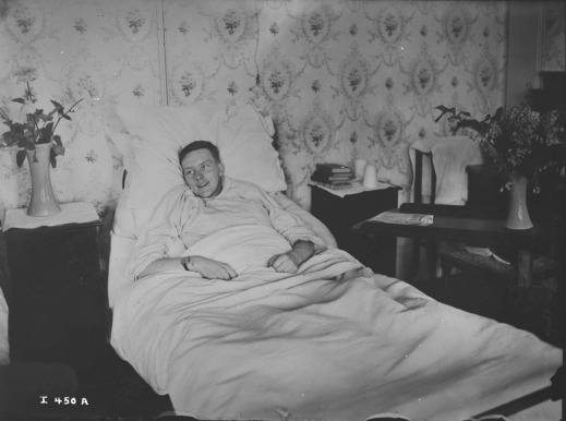 A black-and-white photograph of a smiling young man lying in bed.