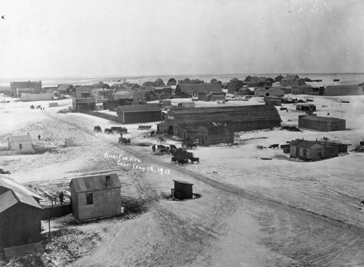 A black-and-white photograph of Cabri, Saskatchewan, from a bird's-eye perspective. It shows a main dirt road with neighbouring houses and buildings. Some people, horses and wagons gather throughout the town.