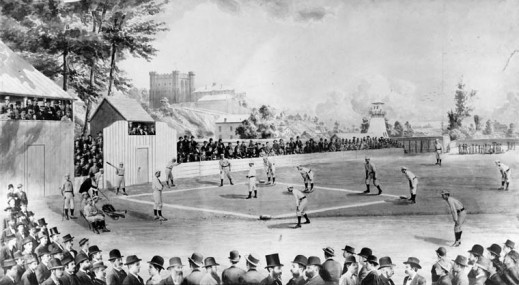 A black-and-white photograph of an outdoor baseball field with a game underway. The crowd watches from the packed stands. The background shows the buildings of the cityscape.
