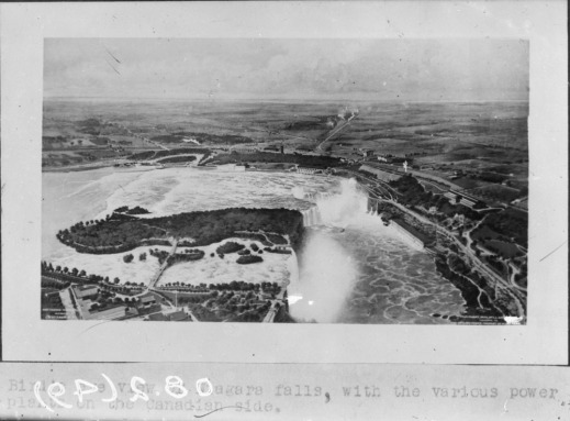 A black-and-white photograph of Niagara Falls from a bird's-eye perspective. There are various buildings on either side of the border and roads leading up to and alongside the riverbanks.