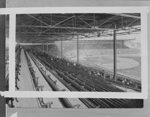 A black-and-white photograph of a baseball stadium, taken from the vantage point of the right field bleachers. The bleachers and the field, including the diamond and outfield, are visible.
