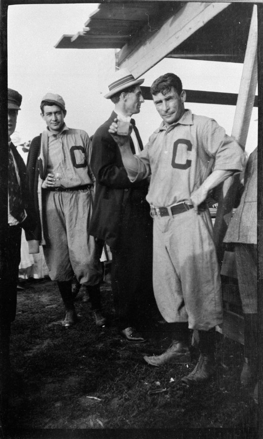 A black-and-white photograph of five men standing around a counter. Two of the men are wearing baseball uniforms with a large letter 'C' on the chest. The other men are wearing suits and hats. One of the uniformed men is holding up a drink and looking towards the camera.