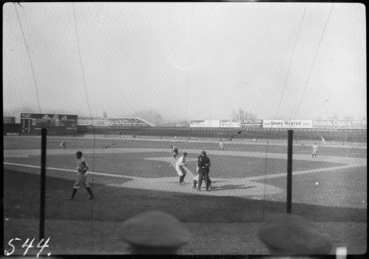 A black-and-white photograph of a baseball game from behind home plate. A player is at the plate as a pitch comes in. The umpire stands behind him to make the call.