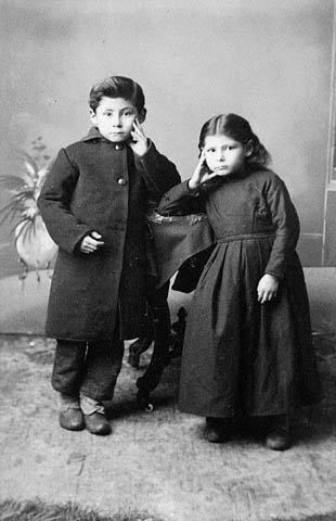 A black-and-white studio photograph of two children leaning against a side table, each with a hand on a cheek.