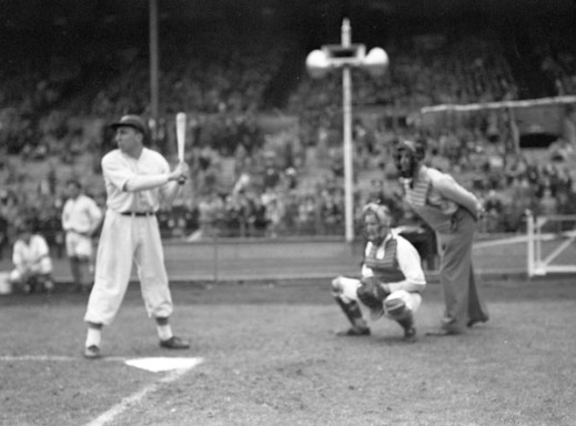 A black-and-white photograph of a baseball game. A player stands with a bat and behind him are a catcher and an umpire. In the background are players watching the play and spectators in the stands.