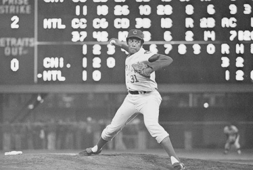 A black-and-white photograph of a pitcher throwing the ball from the mound. Behind him is a large score board displaying the score and outfielders preparing for the ball to come into play.