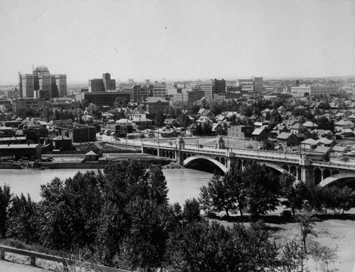 A black-and-white photograph of Calgary, Alberta, from a bird's-eye perspective. The Bow River and a bridge are in the foreground with a number of homes and larger buildings in the background.