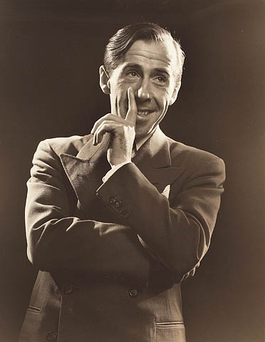 Black-and-white photograph of a man dressed in a suit, with his arms folded and his left hand resting on his cheek, smiling and looking up to his left.