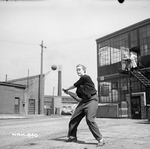 A black-and-white photograph of a woman in work clothes and a headscarf swinging a baseball bat at a ball. She stands in a vacant lot with industrial buildings and other structures in the background.