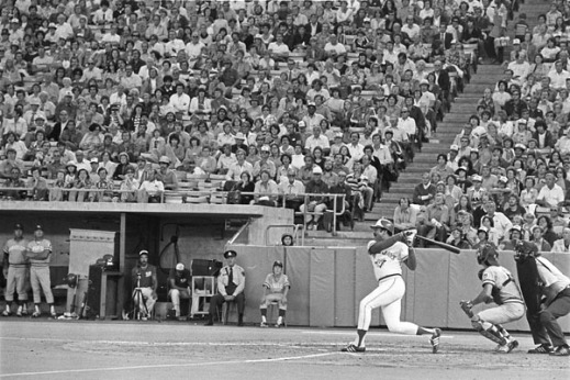 A black-and-white photograph of a baseball game. There's a man who has just swung at the ball. Behind him is a man wearing catcher equipment and crouching, while behind him is an umpire, also crouching. In the background are players in baseball uniforms and a man wearing police uniform, all watching the action. Behind them spectators are seated in the stands.