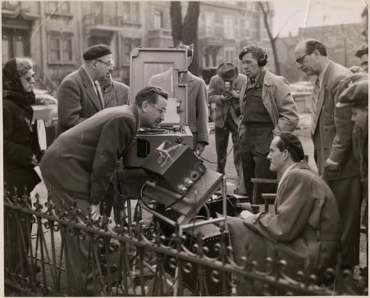 Black-and-white photograph of a film scene showing various people gathered around a camera.