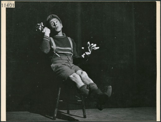 Black-and-white photograph showing a man dressed as a boy in short pants with suspenders, a sweater and a cap, sitting on a chair with his legs extended out in front of him.