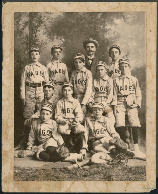 "A black-and-white photograph of 10 children wearing baseball uniforms. The jerseys read ""Pages"" across the front. The boys are sitting and standing with bats, gloves and other baseball equipment. Behind the boys stands an adult man, wearing a suit and hat. The background is a studio backdrop showing trees."