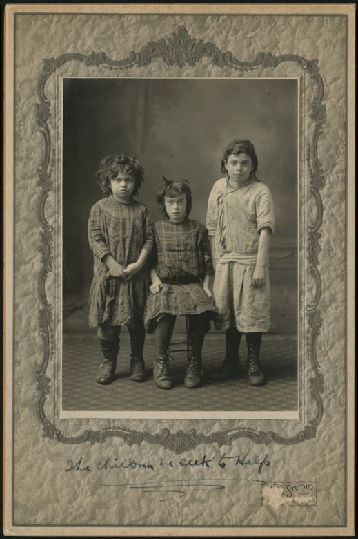 A black-and-white studio photograph of three children. One is sitting in a chair and the two others stand beside.
