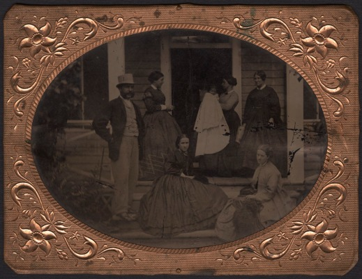 A framed black-and-white photograph of five women, a baby, a man and a dog on a porch posing for a family portrait.