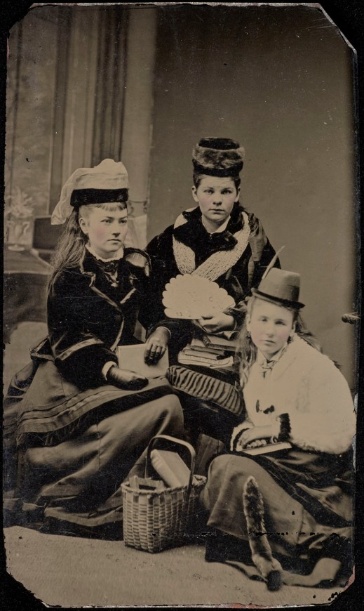 A black-and-white photograph of three women sitting on the ground posing for a portrait. The women are wearing long dresses, short coats, hats, and are holding books.