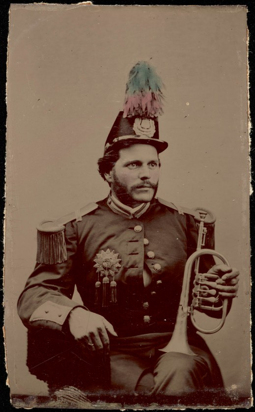 A black-and-white photograph of a man sitting, wearing a band uniform and cap with feathers. The man is holding a flugelhorn resting on his left knee.