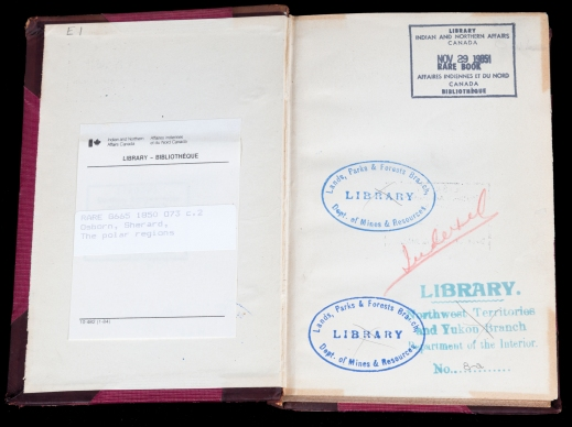A colour photograph of the front endpapers of an open book showing a bookplate on the left-hand page and four stamps on the right-hand page.