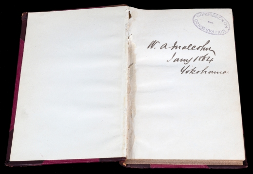 A colour photograph of two pages of an open book showing a stamp and a signature on the right-hand page.
