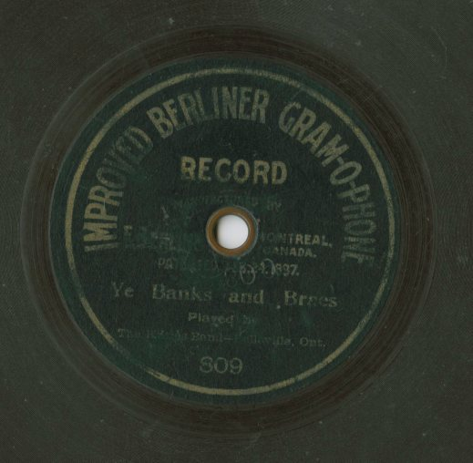 "A colour photograph of a record label that reads ""Improved Berliner Gram-O-Phone Record. Manufactured by [illegible] Montreal, Canada. Patented [illegible] 1897. Ye Banks and Braes. Played by The Kilties Band – Belleville, Ont."""