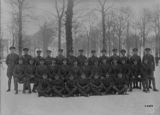 A black-and-white photograph of a group of soldiers standing and sitting in front of trees in the winter.
