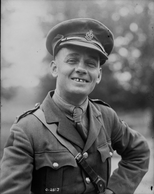 A black-and-white photograph of a smiling military officer.