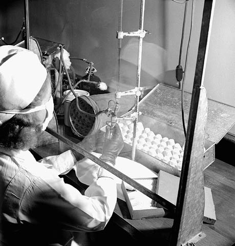 A black-and-white photograph of a woman filling 20-cc vials with penicillin at the Connaught Laboratory.