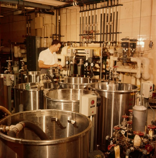 A colour photograph of a man in a chemical mixing laboratory preparing various fluids used in developing processes at the National Film Board of Canada.