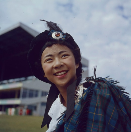 A colour photograph of a smiling girl wearing a tam and tartan shoulder accessory.