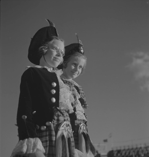 A black-and-white photograph of two girls who are standing and wearing tams, matching jackets and kilts.