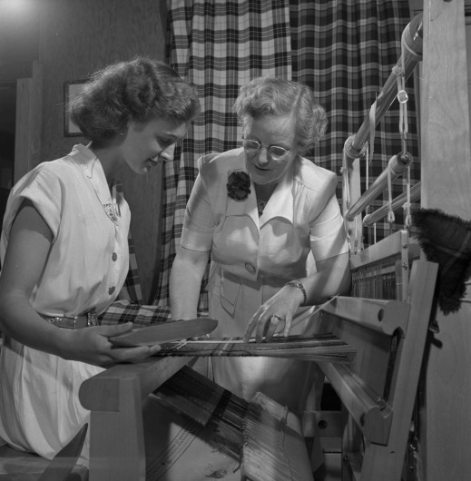 A black-and-white photograph of two women at a loom. The woman sitting on the left holds a shuttle. The woman standing on the right inspects the tartan pattern and weave.