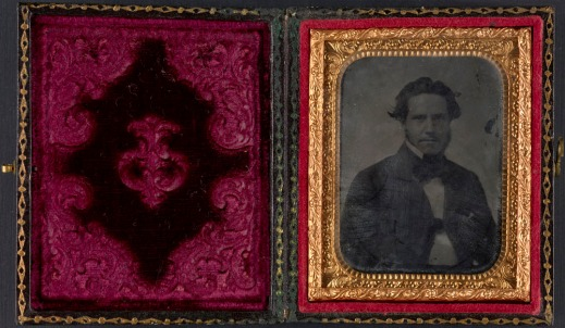 A colour image of a paper case with red velvet. On the right-hand side, a black-and-white photograph in a brass mat of a man wearing a dark jacket.